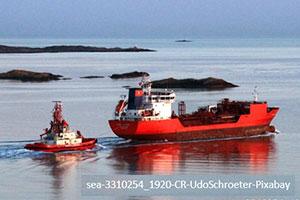 a red cargo ship at sea